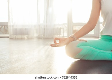 Close up hands of Young attractive woman practicing yoga Mudras at her Fingertips, sitting in lotus pose with hands mudra near a big window with sun light at home, copy space