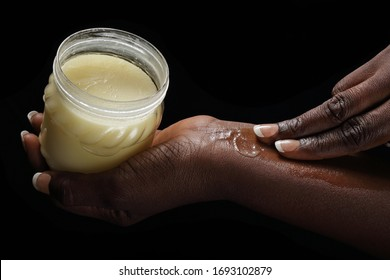 close up hands of a young black african woman smearing shea butter on black studio background
