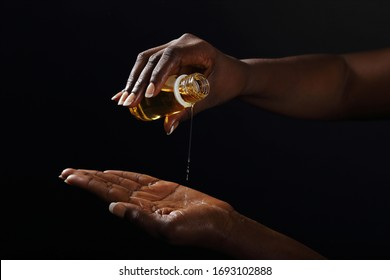 close up hands of a young black african woman smearing jojoba oil on black studio background