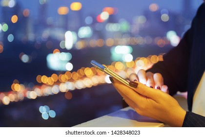 Close up hands of young businesswoman using smart phone against background of city light at night, business and technology concept