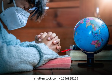 Close up hands of young christian in mask praying for globe in morning, stop Disease Virus and War in the world, christian pray concept.