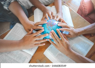 Close up hands of young christian praying for globe and people around the world on wooden table with bible.