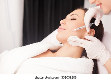 Close up of hands of young cosmetologist injecting botox in female face. She is standing and smiling. The woman is closed her eyes with relaxation