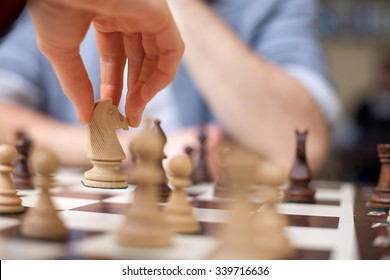 Close up of hands of young man and woman playing chess. They are sitting opposite each other