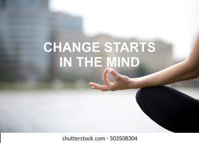 """Close up of hands of young office yogi woman sitting in yoga Easy Sukhasana Pose on riverbank in the city, meditating with fingers in Jnana mudra. Motivational text """"Change starts in the mind"""""""