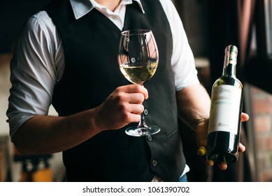 Close up of hands of young sommelier presenting a bottle of red wine he is standing in cellar