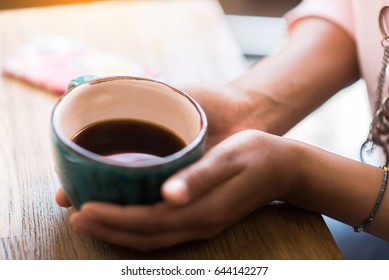 Close up of hands of young woman drinking coffee while sitting at table