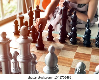 Close up of hands of young  woman playing chess.