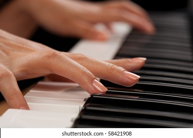 Close up of the hands of a young woman playing piano