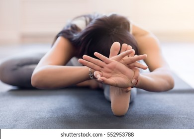 Close up of the hands of a young woman practicing yoga on a black mat