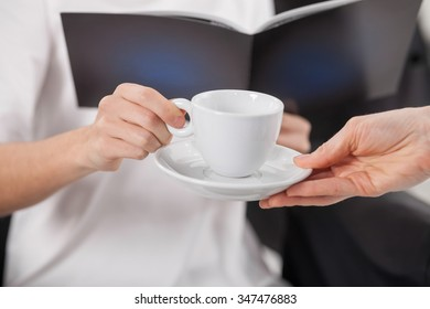 Close up of hands of young woman sitting at beauty salon. The hairdresser is giving her a cup of tea. The lady is reading a magazine