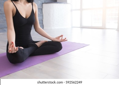 Close up of hands young woman working out on fitness mat, doing lotus yoga pose at the gym. Yoga exercise, relax and meditating, copy space.