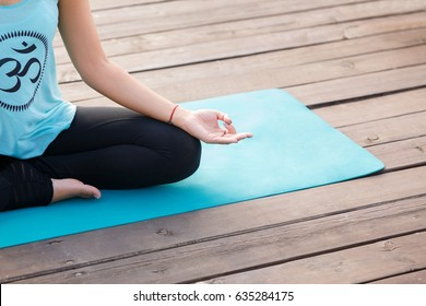 Close up of hands young woman working out on fitness mat, doing lotus yoga pose at the nature by the lake. Yoga exercise, relax and meditating, copy space.