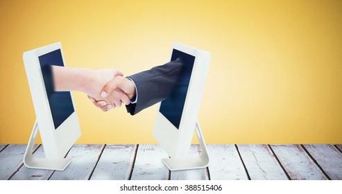 Close up of a handshake against orange background