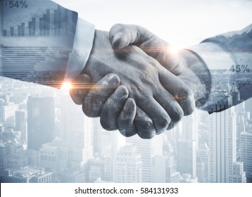 Close up of handshake on abstract city background.Teamwork concept. Double exposure. Filtered image