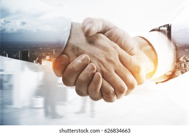 Close up of handshake on abstract city background. Double exposure. Teamwork concept