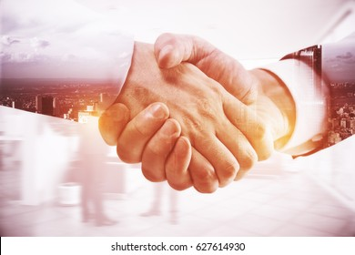 Close up of handshake on abstract city background. Double exposure. Team work concept