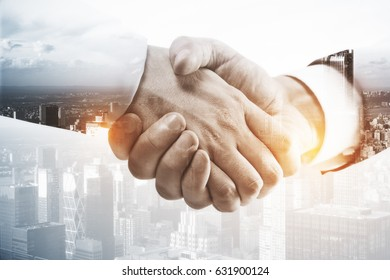 Close up of handshake on abstract city background. Double exposure. Partnership concept