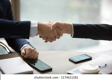Close up handshake of two successful boss ceo male and woman after good deal. Broker and client shaking hands after sales negotiations, greeting at meeting, signing contract, collaboration, HR concept