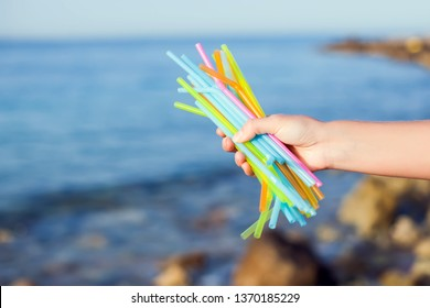 Close Up Of HandsHolding Plastic Straws Polluting Beach. Environmental pollution concept
