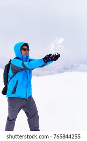 close up of handsome asian male wearing blue jacket, black glove and sunglasses. he is playing snow on the murodo mountain in tateyama alpine route,japan. winter japan and tourism concept.