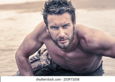 Close up Handsome Athletic Army with No Shirt Crawling at Sea Water While Looking at the Camera.