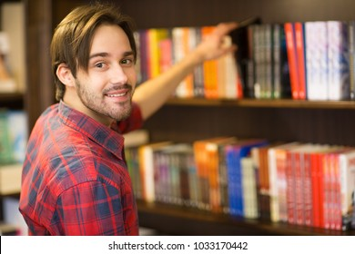 Close up of a handsome bearded young man smiling to the camera over his shoulder while picking a book from the shelf at the library or bookstore copyspace lifestyle student learner college campus.