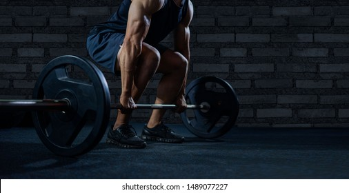 Close up of handsome bodybuilder guy prepare to do exercises with barbell in a gym.bodybuilder's hand is lifting the barbell and exercising in the gym.low key