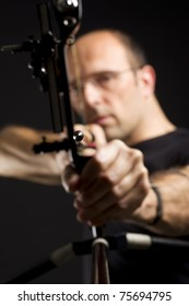 Close up of handsome bowman in black on black background aiming with bow and arrow, front view with focus on arrow tip.