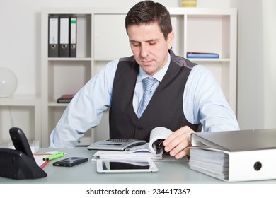 Close up Handsome Businessman Calculating Sales at his Worktable with Various Stuff like Phones, Tablet Computer and Reports