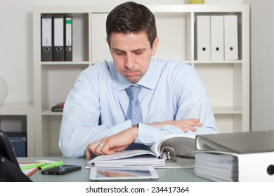 Close up handsome businessman reviewing report papers seriously at his worktable at the office.