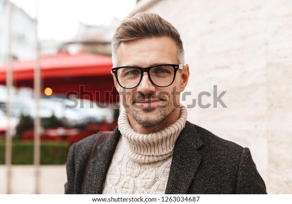 Nahaufnahme eines gut aussehenden Mannes mit einem Mantel, der im Freien spaziert