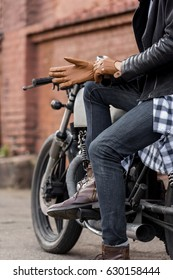 Close up of a handsome rider biker guy hand puts on a leather glove while sit on classic style cafe racer motorcycle. Bike custom made in vintage garage. Brutal fun urban lifestyle. Outdoor portrait.