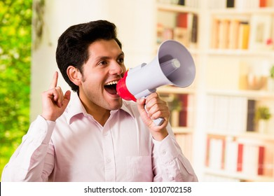 Close up of a handsome smiling man screaming with a megaphone in a blurred background