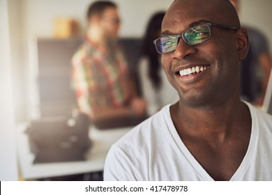 Close up of handsome smiling worker in white shirt and eyeglasses with three out of focus employees behind him in meeting