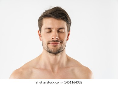 Close up of a handsome smiling young shirtless man isolated over white background, eyes closed
