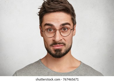 Close up of handsome young male with beard and mustache, looks through spectacles with indignant expression, can`t understand something, has serious and upset expression, poses in white studio