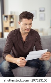 Close up Handsome Young Man in Casual Clothing, Reading a Letter Seriously While Sitting at the Couch In the Living Room.