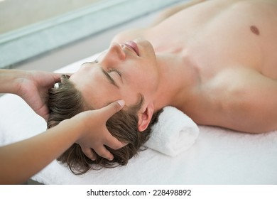 Close up of a handsome young man receiving head massage at spa center