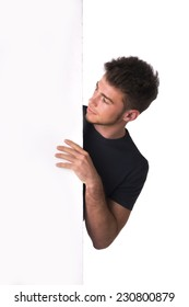 Close up Handsome Young Man Wearing Casual Black Shirt Peeking Behind Plain White Wall.