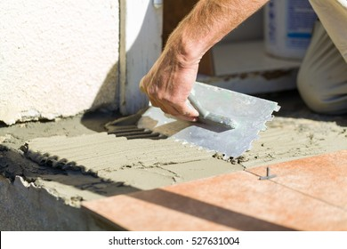 Close up of handyman affixing adhesive grout to get tiled concrete before the front door.