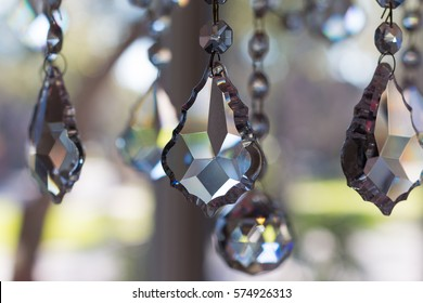 Close Up of Hanging Crystal Glass Light Fixture. Glass shaped crystal design from a light fixture with transparent views of luxury. Heavy blur background.