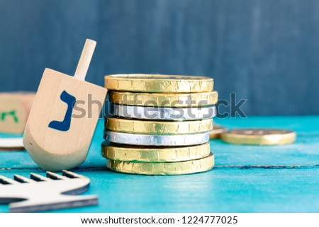 Close up of Hanukkah gelt or money or coins with Hanukkah dreidel. Translation of the hebrew text: Happy Holidays and Letter N