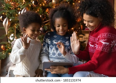 Close up happy African American family making video call to relatives on Christmas, sitting near festive tree at home, smiling mother with two kids using tablet, chatting online, waving hands