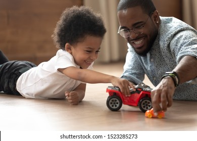 Close up happy african american man in eyeglasses and cute curly kid son playing with plastic auto cars toys, having fun together, spending active weekend, lying on heated floor at living room.