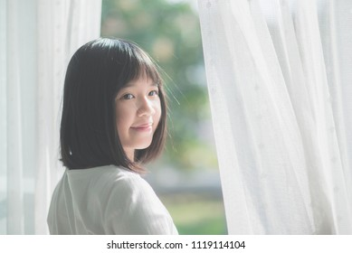 close up of happy Asian girl opening window curtains