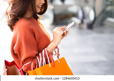 Close up happy Asian pretty girl holding shopping bags while using smartphone at shopping mall background concept.