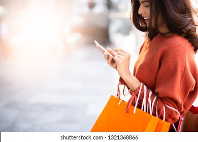 Close up happy Asian pretty girl holding shopping bags while using smartphone background shopping mall concept.