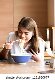 Close up happy asian woman using chopsticks for eating noodle at restaurant,lunch time concept.