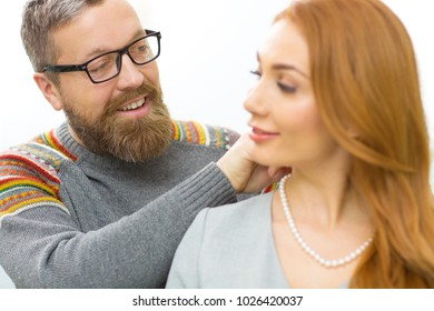 Close up of a happy beautiful cpuple trying pearl necklace at the jewelry store love romance valentines gift present affection happiness relationships dating marriage retail consumerism purchase.